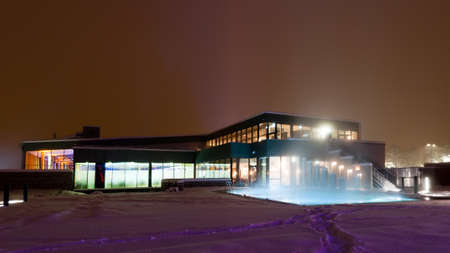 modern building with differnt light colors of a swimming pool at night on a winters day Standard-Bild