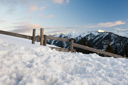romantic tyrolean mountains at twilight with much snow, wooden fence and blue cloudy sky Stock Photo