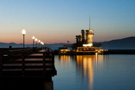 balk:  lighted tower beacon with restaurant next to a catwalk at dawn with nice mirroring in the water