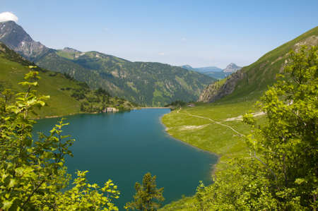 tal: lovely mountain lake in the middle of the tannheimer tal with green meadow and blue sky Stock Photo
