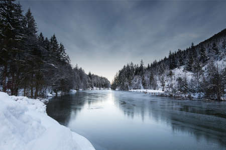 view to a winter landscape with frozen lake plansee and snowy forest in tyrol austria photo