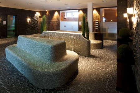 mozaïek betegelde zitgroep voor wellness met diverse sauna en stoom kamers rond, met sfeervolle en indrukwekkende bliksem Stockfoto