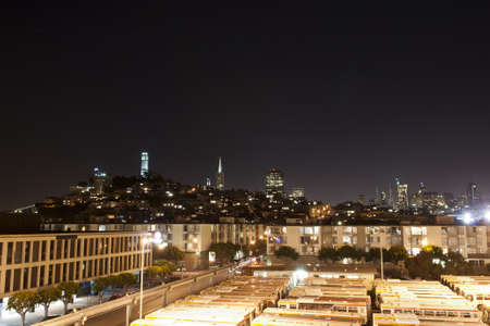 coit: night panorama of san francisco Coit Tower and a lot of orange busses in the front  Stock Photo