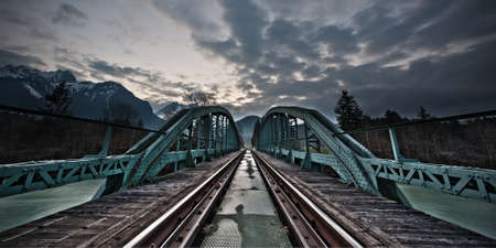 painted framework bridge and rails at sunset with dramatic cloudy sky photo