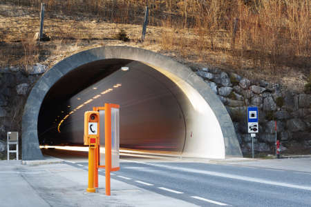 start of a conrete tunnel with fading lights of traffic and orange emergency telephone booth Stock Photo