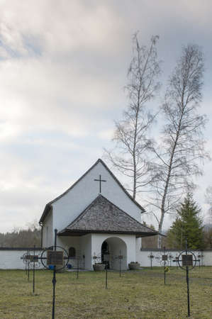 black death graveyard chapel with a lot of crosses in front and two huge birch trees photo