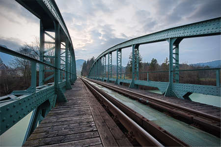 wood railroad: railway train bridge with cyan painted steel framework over river