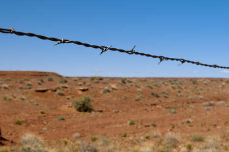 cattle wire wire: barbed wire as divider to the hot red desert with blue sky Stock Photo