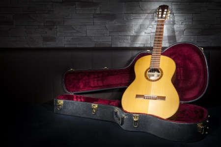 string instrument: illuminated classic music guitar with case in front of leather and stone wall
