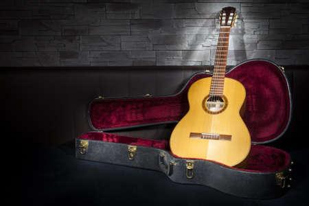 verlichte klassieke muziek gitaar met case in de voorkant van leer en stenen muur