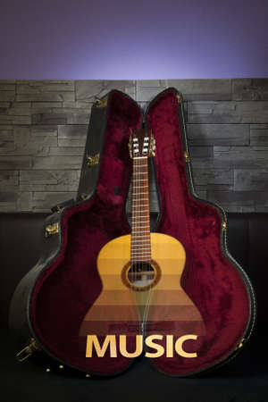 illuminated classic music guitar with case in front of leather and stone wall photo