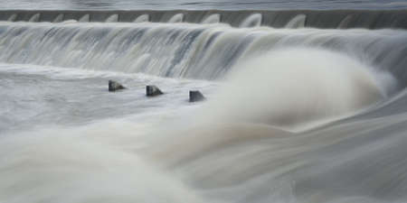 seething: river water step with flowing water and spume with concrete elements Stock Photo