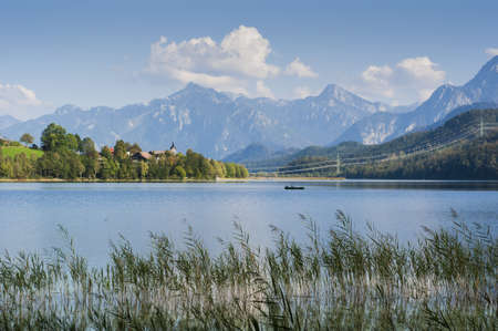 bavarian landscape with lake and fisher boat and tyrolean mountains and reed in the front photo