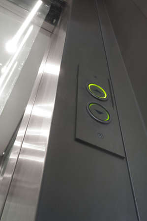 lift hands: green illuminated elevator buttons and glass and aluminium door opening