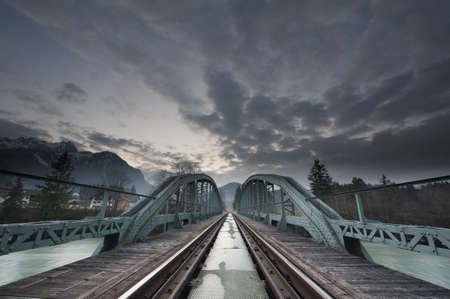 railway history: mystical train bridge made of steel and dramatic sky at sunset
