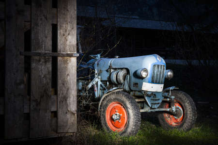 blue oldtimer farming tractor standing next to a wooden hut at night with red painted tires photo