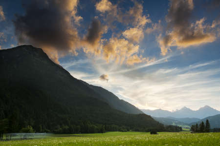 Lush green meadow in a mountain valley at sunset surrounded by silouetted peaks under glowing orange clouds photo