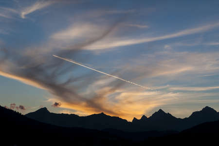 silhoutted: Beautiful orange sunset and contrail from a jet aifcraft over a rugged silhoutted mountain range Stock Photo