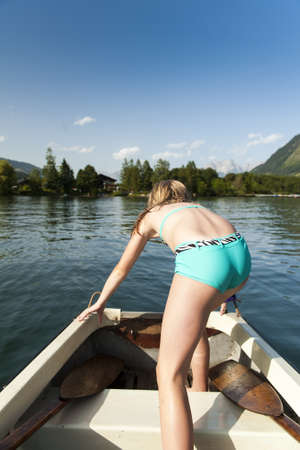 onboard: Young girl in a rowboat standing up with her back to the camera stepping over the seat to reach the stern to dive into the water for a swim Stock Photo