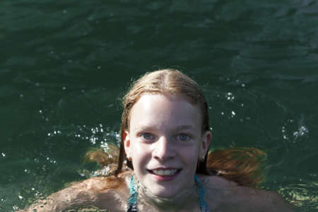 wet girl: Attractive teenage girl with a lovely merry smile swimming in a lake with sunlight on the water and copyspace