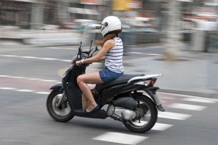 vespa: Mujer que monta una motocicleta por una calle urbana en pantalones cortos y top del verano con el desenfoque de movimiento Foto de archivo