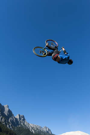 high jump: dirt biker makes a high backflip with blue sky and mountains in the background Stock Photo