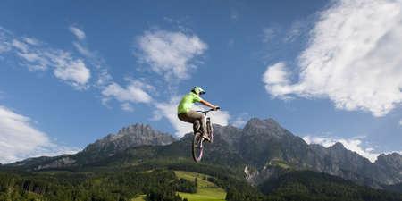 jonge freestyler sprongen met zijn BMX hoog in de lucht met mooie natuur, bergen en bewolkte hemel in de rug