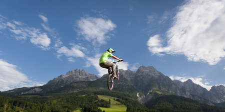 young freestyler jumps with his bmx high into air with nice nature, mountains and cloudy sky in the back photo