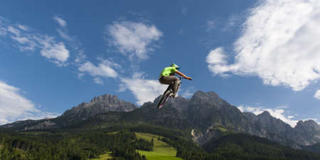 young freestyler jumps with his bmx high into air with nice nature, mountains and cloudy sky in the back Stock Photo - 15471959
