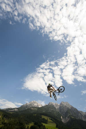 young freestyler jumps with his bmx high into air with nice nature, mountains and cloudy sky in the back