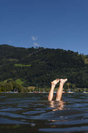 just the legs of a teenager are over the water surface of lake zell am see photo