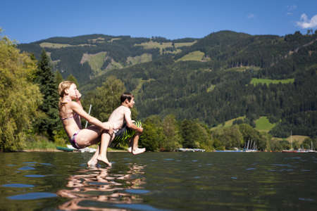 two young kids jumping into the lake zell am see at a nice summer day