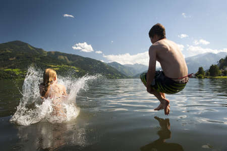 children jumping: girl already in the splashing water and boy in the air while they where jumoing into a lake, with nice nature and mountains in the back