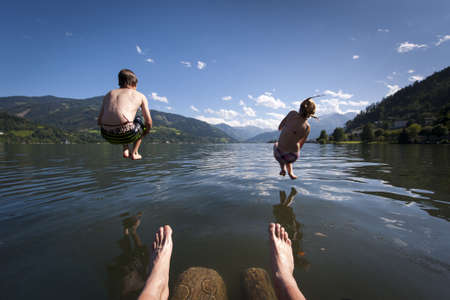 two kids in the air while jumping into lake with legs of the photographer with nice summer nature scenery Stock Photo