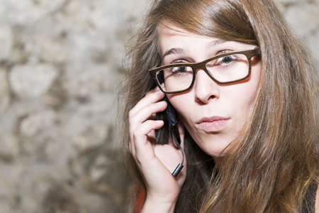 copysapce: Attractive young woman wearing glasses reacting in surprise to the conversation on a mobile, natural expression with copysapce Stock Photo