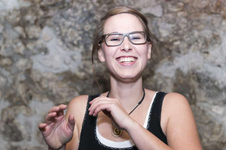 merriment:   a young woman in glasses laughing happily at a good joke against a mottled background