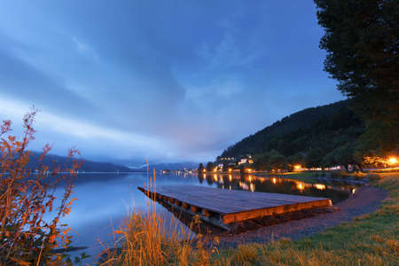 Sunset over a tranquil lake with a wooden jetty and colourful lights lining the shore photo