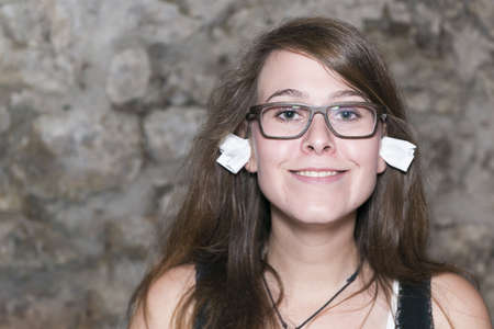 daft: Pretty geek girl with eyeglasses and ear plugs in her ears Stock Photo