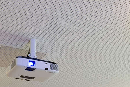audiovisual: turned on lcd video projector with ceiling suspension