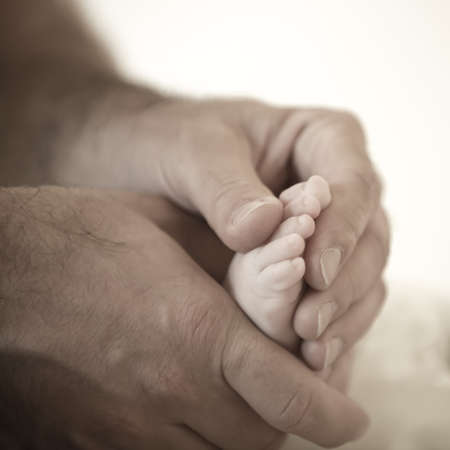 hairy hands of the father are holding the tiny toes of baby