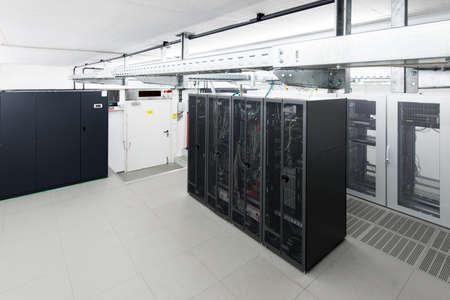kleine airconditioning server ruimte met zwarte rekken en klimaat controle-eenheid