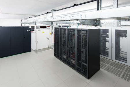 small air conditioned server room with black racks and climate control unit