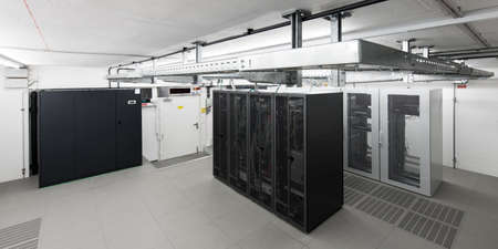 wide angle view of small air conditioned computer room with racks an cable trays