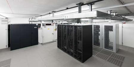 brede kijkhoek van kleine airconditioning computerlokaal met racks een kabelgoten Stockfoto