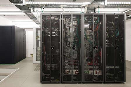achterzijde van gearrangeerde zwarte server racks in kleine computerruimte