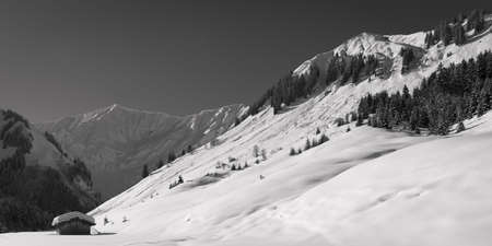 winter landscape in austrian alps with snowy peaks and small hut photo