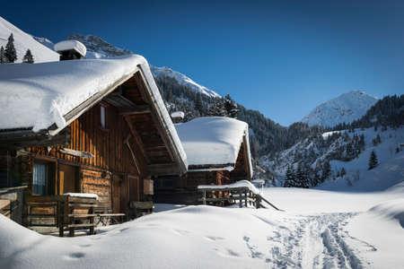 montañas nevadas: casas de madera en las montañas de Austria en invierno con mucha nieve
