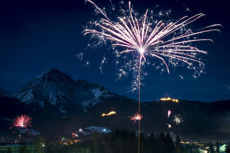 fire show: New Years Eve fireworks rocket flying upwards before mountains