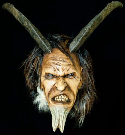 houten satan kwaad masker met hoorns en bont baard op zwart Stockfoto