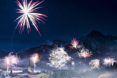 rockets firework at new years day in front of snowy mountains photo